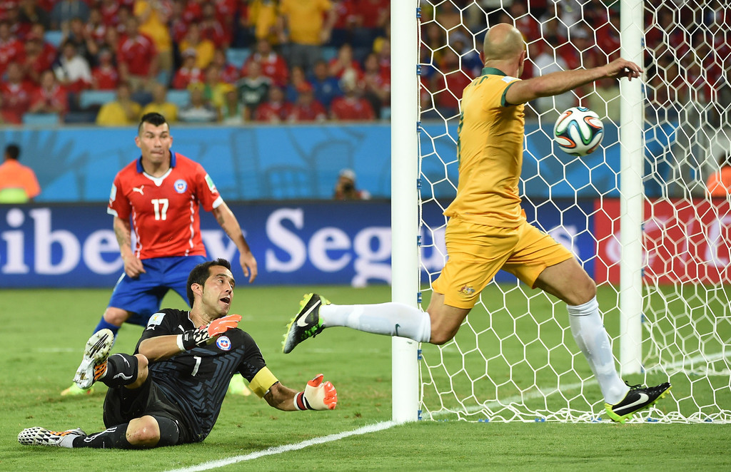 . Chile\'s goalkeeper Claudio Bravo (L) and Australia\'s midfielder Mark Bresciano (R) vie for the ball during a Group B football match between Chile and Australia at the Pantanal Arena in Cuiaba during the 2014 FIFA World Cup on June 13, 2014.     AFP PHOTO / WILLIAM WEST