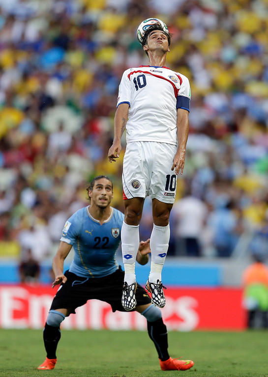 . Costa Rica\'s Bryan Ruiz (10) heads the ball over Uruguay\'s Martin Caceres (22) during the group D World Cup soccer match between Uruguay and Costa Rica at the Arena Castelao in Fortaleza, Brazil, Saturday, June 14, 2014.  (AP Photo/Natacha Pisarenko)