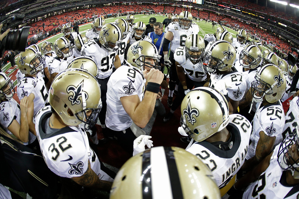 . New Orleans Saints quarterback Drew Brees (9) cheers with the team before the first half of an NFL football game against the Atlanta Falcons, Thursday, Nov. 21, 2013, in Atlanta. (AP Photo/John Bazemore)