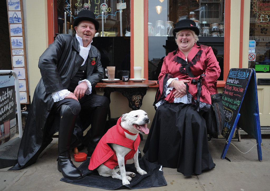 . WHITBY, ENGLAND - NOVEMBER 02: A couple of Goths pose and their dog as they relax in a cafe as they visit the Goth weekend on November 2, 2013 in Whitby, England. The Whitby Gothic Weekend that takes place in the Yorkshire seaside town twice yearly in Spring and Autumn started in 1994 and sees thousands of extravagantly dressed followers of Victoriana, Steampunk, Cybergoth and Romanticism visit to take part in celebrating Gothic culture.  (Photo by Ian Forsyth/Getty Images)