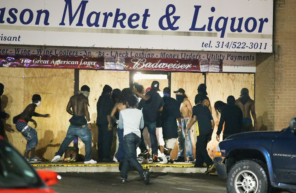 . FERGUSON, MO - AUGUST 16: People loot the Ferguson Market and Liquor store on August 16, 2014 in Ferguson, Missouri. Several businesses were looted as police held their position nearby. Violent outbreaks have taken place almost daily in Ferguson since the shooting of Michael Brown by a Ferguson police officer on August 9.  (Photo by Scott Olson/Getty Images)