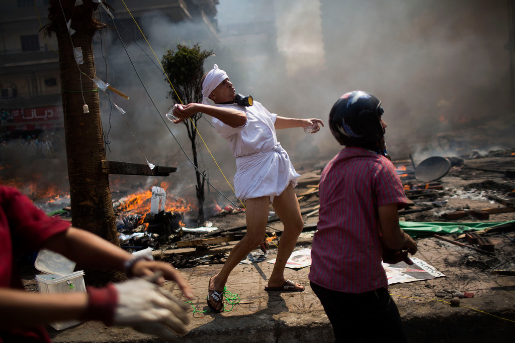 . A supporter of ousted Islamist President Mohammed Morsi throws a drinking glass during clashes with Egyptian security forces in Cairo\'s Nasr City district, Egypt, Wednesday, Aug. 14, 2013.  (AP Photo/Manu Brabo)