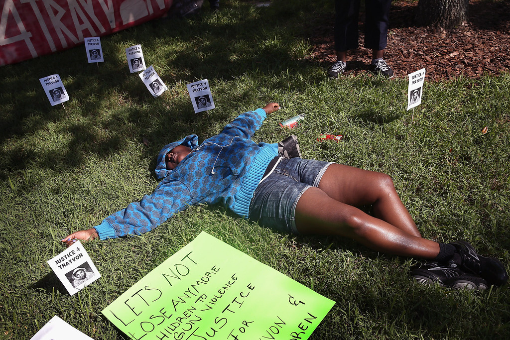 . SANFORD, FL - JULY 13:  A protestor portrays a dead Trayvon Martin in front of the Seminole County Criminal Justice Center where a jury is deliberating in the trial of George Zimmerman on July 13, 2013 in Sanford, Florida. Zimmerman, a neighborhood watch volunteer, is on trial for the February 2012 shooting death of 17-year-old Trayvon Martin.  (Photo by Scott Olson/Getty Images)