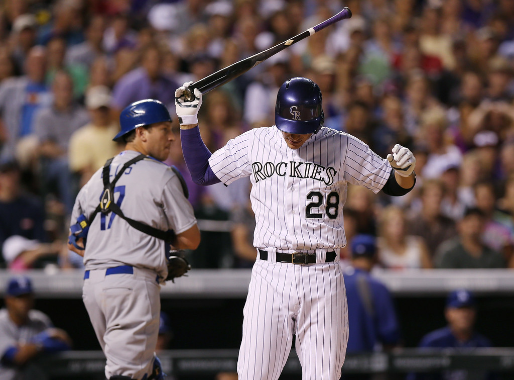 . Colorado Rockies\' Nolan Arenado, front, reacts after striking out with two runners on base as Los Angeles Dodgers catcher A.J. Ellis heads to the dugout at the end of the eighth inning of the Dodgers\' 3-2 victory in a baseball game in Denver on Thursday, July 3, 2014. (AP Photo/David Zalubowski)
