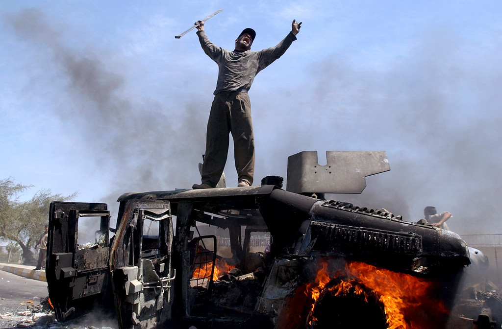 . An Iraqi man celebrates atop of a burning U.S. Army Humvee in the northern part of Baghdad, Iraq, Monday, April 26, 2004. An explosion leveled a building in northern Baghdad, setting four U.S. Humvees nearby on fire. At least one U.S. soldier and several Iraqis were wounded. The cause of the explosion was not immediately known. (AP Photo/Muhammed Muheisen)