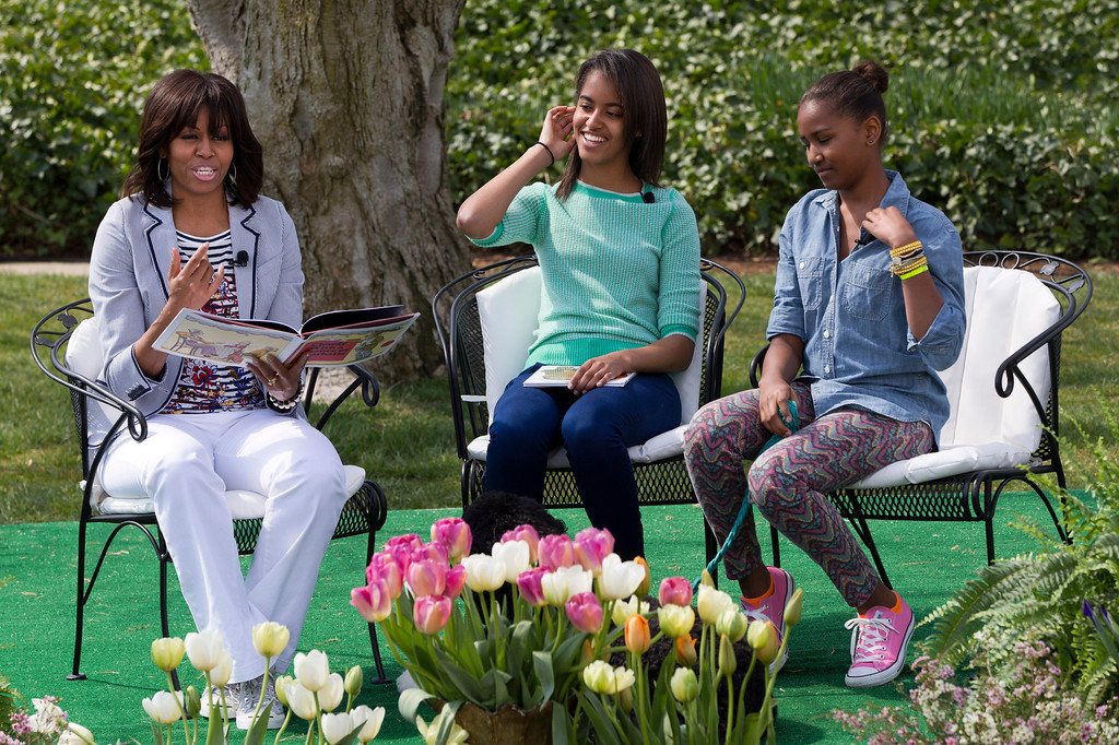 """. First lady Michelle Obama, with daughters Malia and Sasha, reads the book \""""Cloudy With A Chance of Meatballs\"""" to children as part of the annual White House Easter Egg Roll, Monday, April 1, 2013, on the South Lawn of the White House in Washington. (AP Photo/Jacquelyn Martin)"""