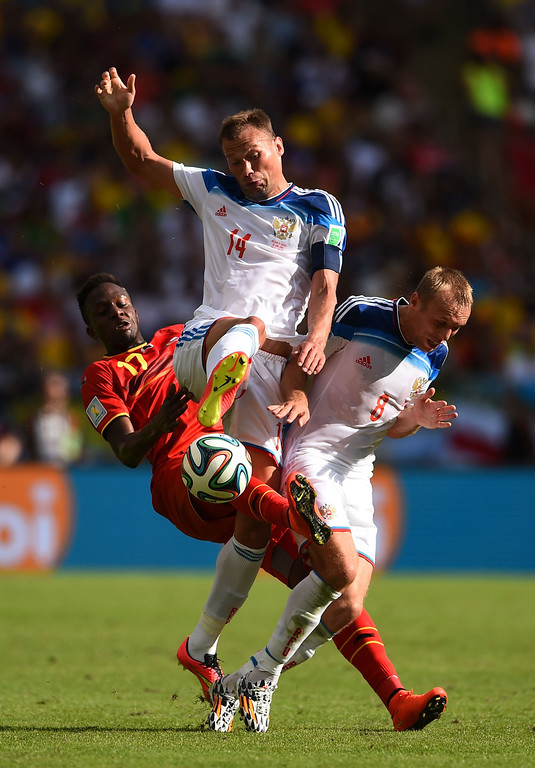 . Divock Origi of Belgium, Vasily Berezutskiy and Denis Glushakov of Russia clash during the 2014 FIFA World Cup Brazil Group H match between Belgium and Russia at Maracana on June 22, 2014 in Rio de Janeiro, Brazil.  (Photo by Matthias Hangst/Getty Images)