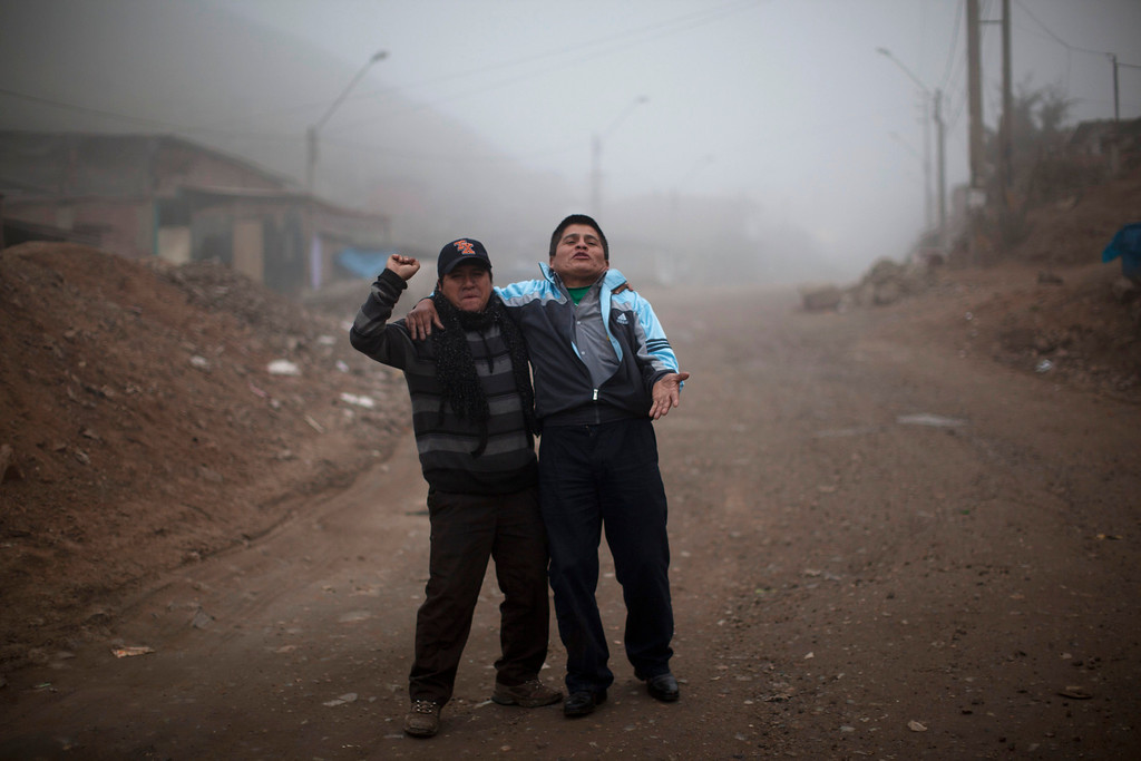 . In this July 17, 2013 photo, two drunk men walk on a dirt road at the Santa Maria neighborhood in Lima, Peru. For roughly four months a year, the sun abandons Peru\'s seaside desert capital, suffocating it under a ponderous gray cloudbank and fog that coats the city with nighttime drizzles. Limenos don scarfs and jackets and complain of slipping into a gloom of seasonal depression. (AP Photo/Rodrigo Abd)