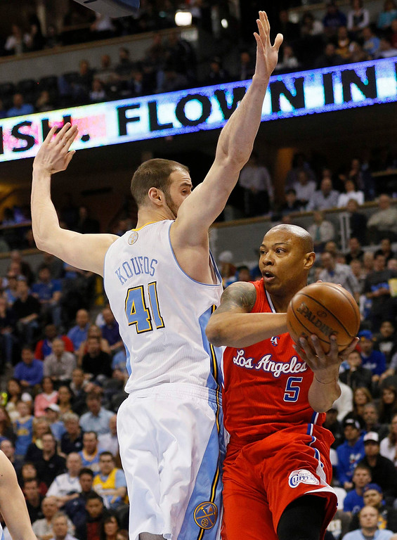 . Los Angeles Clippers\' Caron Butler (R) tries to get past Denver Nuggets\' Kosta Koufos in their NBA basketball game in Denver March 7, 2013. REUTERS/Rick Wilking