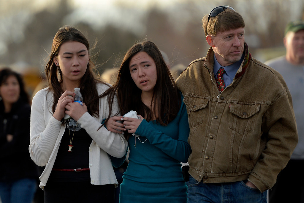 . CENTENNIAL, CO. - December 13: 15 year olds (left) Aili Miyake and her best friend Kasina Wootten leave with Kasina\'s father Chris Wootten from the Shepherd of the Hills church during a lockdown when a student carried a shotgun into Arapahoe High School and opened fire on Friday, wounding two fellow students before apparently killing himself December 13, 2013 Centennial, CO. (Photo By Joe Amon/The Denver Post)