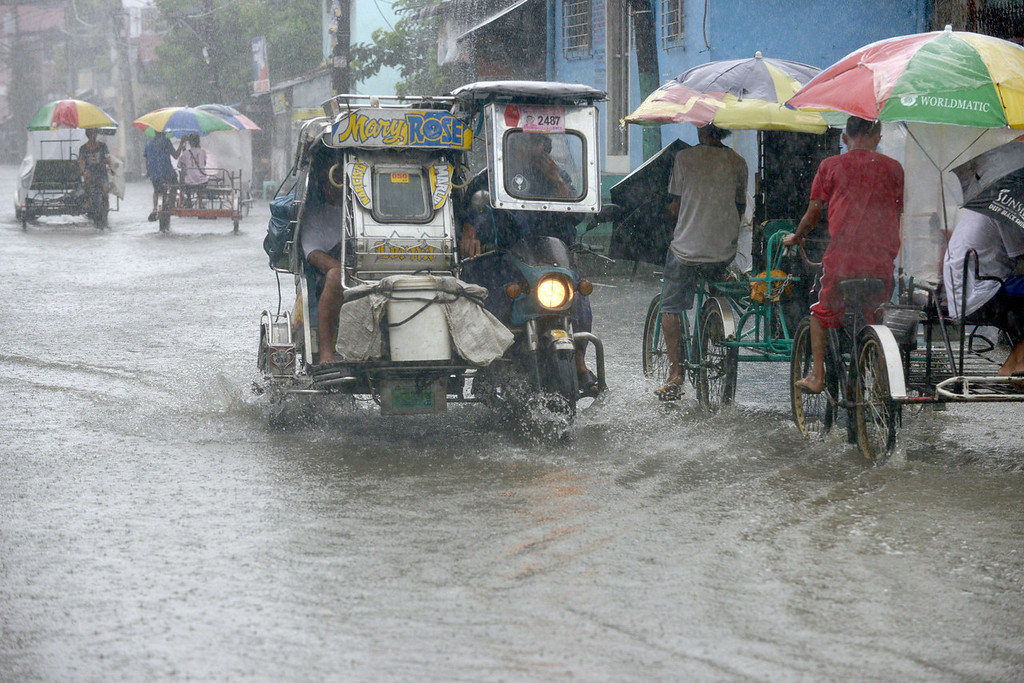. Residents commute along a flooded stretch of road during heavy rain in the suburbs of Manila on August 12, 2013. The strongest typhoon to hit the Philippines this year flattened houses and triggered landslides in remote towns on August 12, killing at least one person and leaving 23 others missing, authorities said.   JAY DIRECTO/AFP/Getty Images