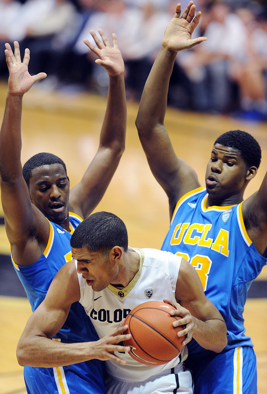 . Josh Scott of CU is trapped by Jordan Adams, left, and Tony Parker, of UCLA, during the second half of the January 16, 2014 game in Boulder.  (Cliff Grassmick/Daily Camera)