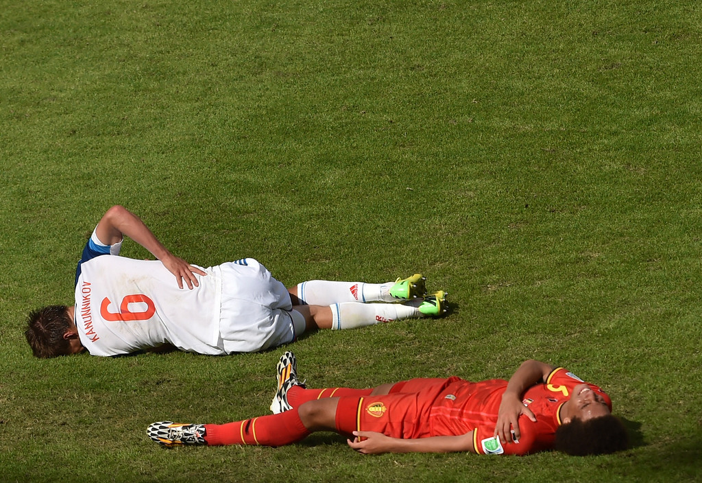 . Russia\'s forward Maksim Kanunnikov (L) and Belgium\'s midfielder Axel Witsel  lie on the ground following a tackle during a Group H football match between Belgium and Russia at the Maracana Stadium in Rio de Janeiro during the 2014 FIFA World Cup on June 22, 2014.   YOSHI CHIBAYASUYOSHI CHIBA/AFP/Getty Images