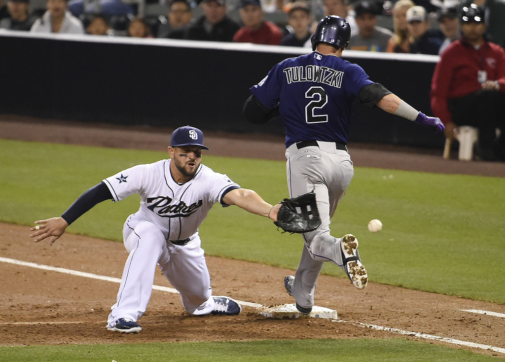 . Yonder Alonso #23 of the San Diego Padres loses the ball as Troy Tulowitzki #2 of the Colorado Rockies goes to first base during the third inning of a  baseball game at Petco Park April 14, 2014 in San Diego, California. The bad throw allowed a run to score.  (Photo by Denis Poroy/Getty Images)