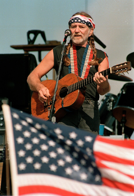 . As Singer Willie Nelson opens his Fourth of July Picnic event in Carl\'s Corner, Texas, on July 4, 1987, a fan in the audience is waving the American flag.  (AP Photo/Bill Janscha)