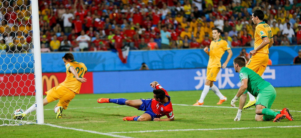 . Australia\'s Alex Wilkinson, left, clears the ball off the line during the group B World Cup soccer match between Chile and Australia in the Arena Pantanal in Cuiaba, Brazil, Friday, June 13, 2014.  (AP Photo/Frank Augstein)