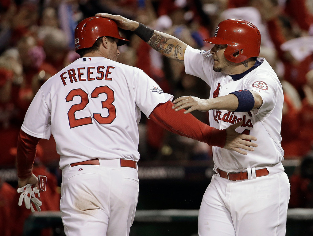 . St. Louis Cardinals\' David Freese and Yadier Molina celebrate after both scored on a hit by Shane Robinson during the third inning of Game 6 of the National League baseball championship series against the Los Angeles Dodgers, Friday, Oct. 18, 2013, in St. Louis. (AP Photo/David J. Phillip)