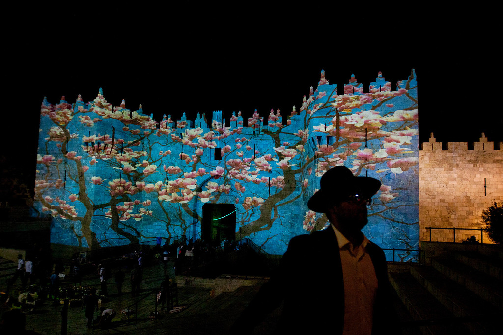 . An ultra-Orthodox Jewish man walks as a light installation is projected onto the Damascus gate during the fifth annual Festival of Light in Jerusalem\'s Old City,  Wednesday, June 5, 2013. (AP Photo/Sebastian Scheiner)
