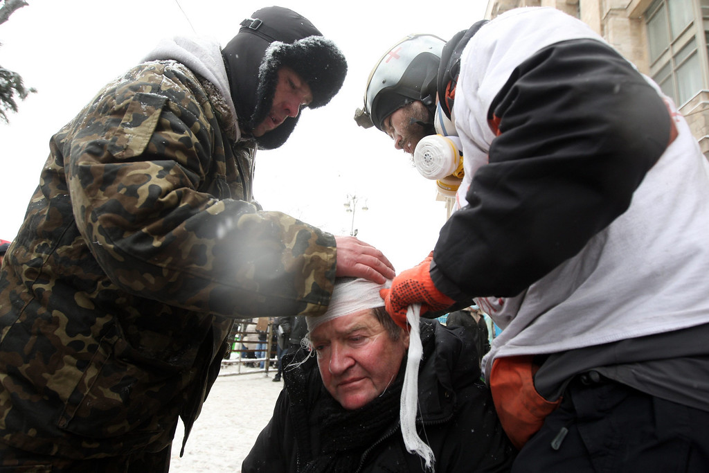 . People help an injured man after clashing with riot police during an anti-government protest in downtown Kiev, Ukraine, 22 January 2014.  EPA/ZURAB KURTSIKIDZE