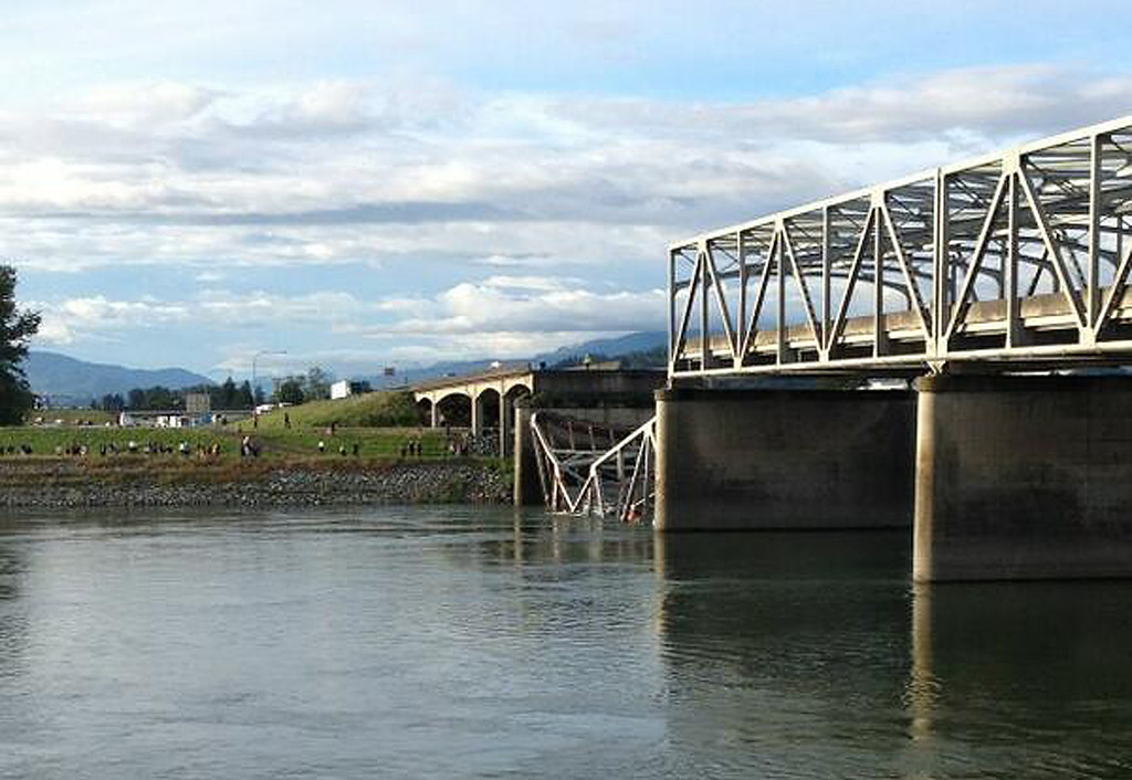 . Vehicles can be seen in the water after a section of the Interstate 5 bridge over the Skagit River, north of Seattle, collapsed Thursday evening, May 23, 2013.   The four-lane bridge collapsed at about 7 p.m., Trooper Mark Francis said. (AP Photo/Skagit Valley Herald, Gina Cole)