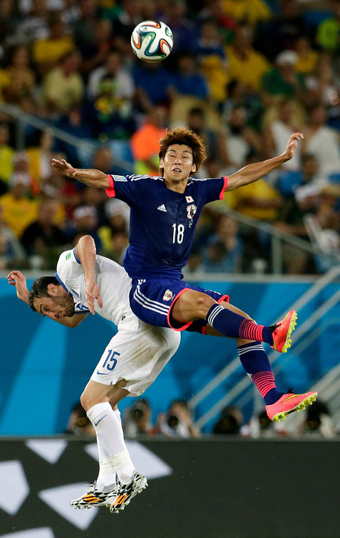 . Japan\'s Yuya Osako, right, leaps over Greece\'s Vasilis Torosidis to head the ball during the group C World Cup soccer match between Japan and Greece at the Arena das Dunas in Natal, Brazil, Thursday, June 19, 2014.  (AP Photo/Petr David Josek)