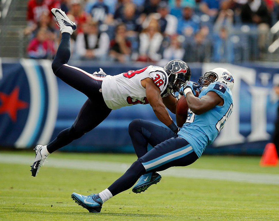 . Tennessee Titans tight end Jared Cook, right, catches a pass as he is defended by Houston Texans free safety Danieal Manning (38) in the first quarter of an NFL football game on Sunday, Dec. 2, 2012, in Nashville, Tenn. (AP Photo/Joe Howell)