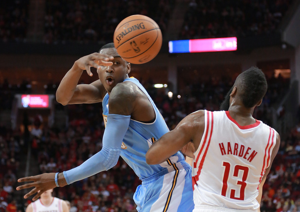 . Denver Nuggets forward Quincy Miller makes a pass around Houston Rockets guard James Harden (13) during the first half of an NBA basketball game in Houston on Sunday, April 6, 2014.  (AP Photo/Richard Carson)