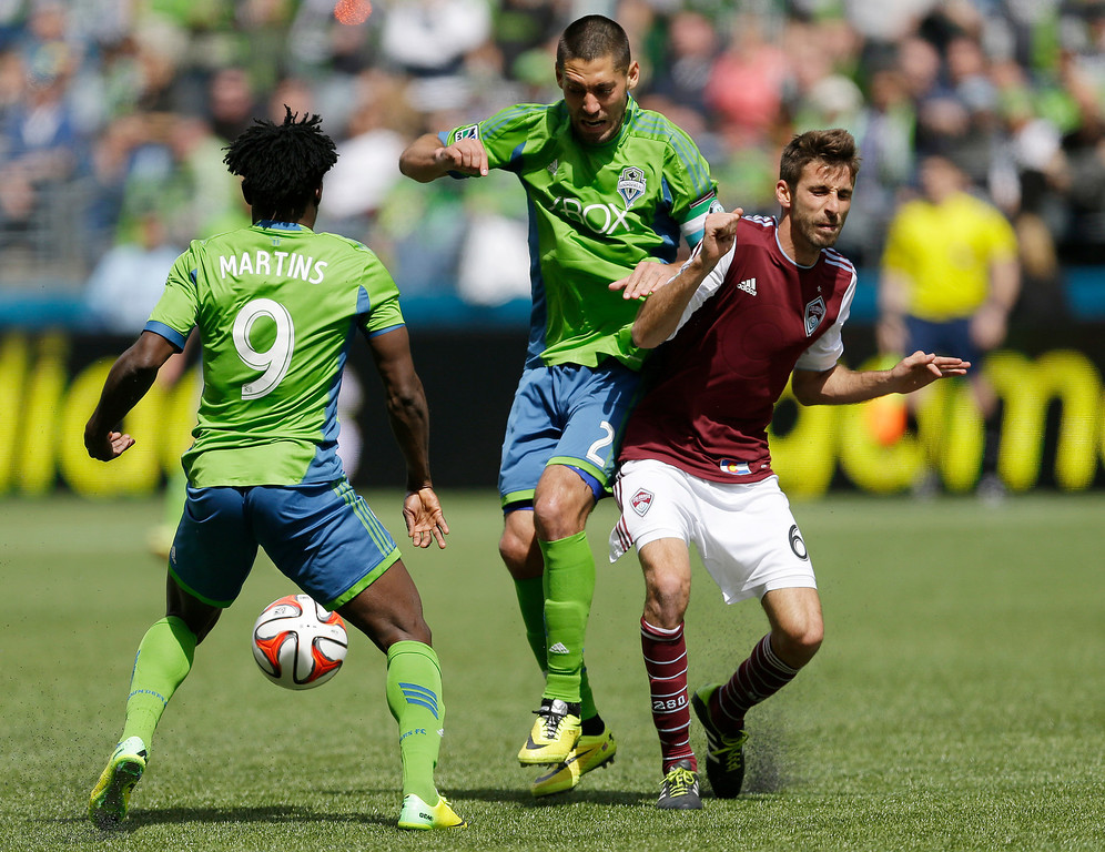 . Seattle Sounders\' Clint Dempsey, center, and Obafemi Martins, left, battle for the ball with Colorado Rapids\' Jose Mari, right, Saturday, April 26, 2014, in the second half of an MLS soccer match in Seattle. (AP Photo/Ted S. Warren)
