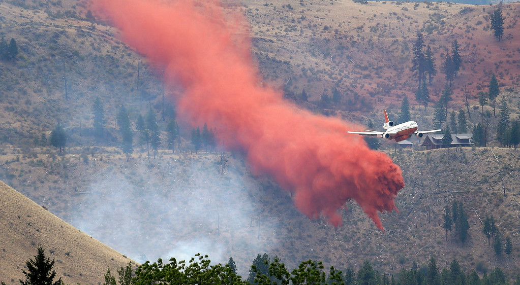 . A DC-10 air tanker pulls up after dropping fire retardant over a wildfire Saturday, July 19, 2014, near Carlton, Wash. A wind-driven, lightning-caused wildfire racing through rural north-central Washington destroyed about 100 homes Thursday and Friday, leaving behind solitary brick chimneys and burned-out automobiles as it blackened hundreds of square miles in the scenic Methow Valley northeast of Seattle. (AP Photo/Elaine Thompson)