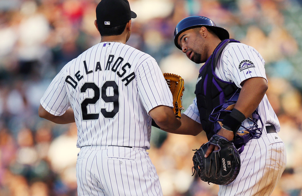 . Colorado Rockies starting pitcher Jorge De La Rosa, left, confers with catcher Wilin Rosario after giving up a wild pitch against the Arizona Diamondbacks in the fourth inning of a baseball game in Denver on Tuesday, June 3, 2014. (AP Photo/David Zalubowski)