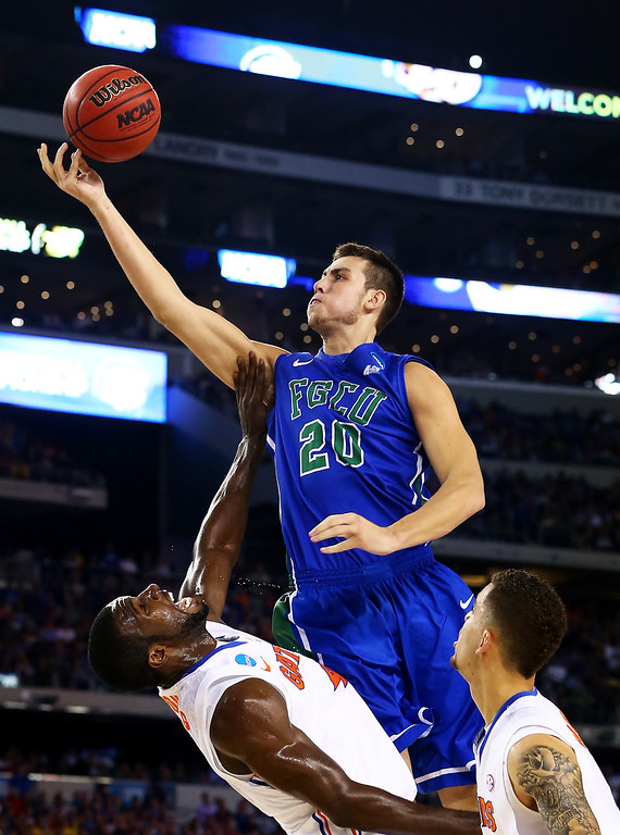 . ARLINGTON, TX - MARCH 29:  Chase Fieler #20 of the Florida Gulf Coast Eagles goes up over Patric Young #4 of the Florida Gators in the first half during the South Regional Semifinal round of the 2013 NCAA Men\'s Basketball Tournament at Dallas Cowboys Stadium on March 29, 2013 in Arlington, Texas.  (Photo by Ronald Martinez/Getty Images)