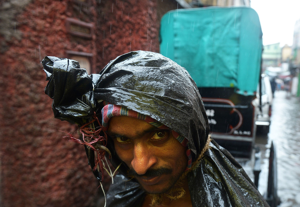 . An Indian rickshaw puller covered with plastic walks through a street during heavy rains  in Kolkata on October 26, 2013.  Persistent rain for the last 24 hours has thrown normal life out of gear with reports of water logging at major arterial roads of the city which received 14 cm rainfall, the highest rainfall during the ongoing depression in eastern India. DIBYANGSHU SARKAR/AFP/Getty Images