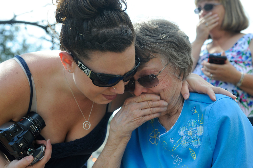 . Cortney Lee, left, hugs her great-aunt, Lauretta Anzalone, 80, as she sees her home burnt to the ground for the first time, her niece, Jayne Lee, Courtney\'s mother, stands close behind at right. Lauretta\'s home was located on Lions Gate Lane in the Mountain Shadow subdivision of Colorado Springs and is one of the many that were destroyed by the Waldo Canyon Fire. Heather Rousseau, The Denver Post