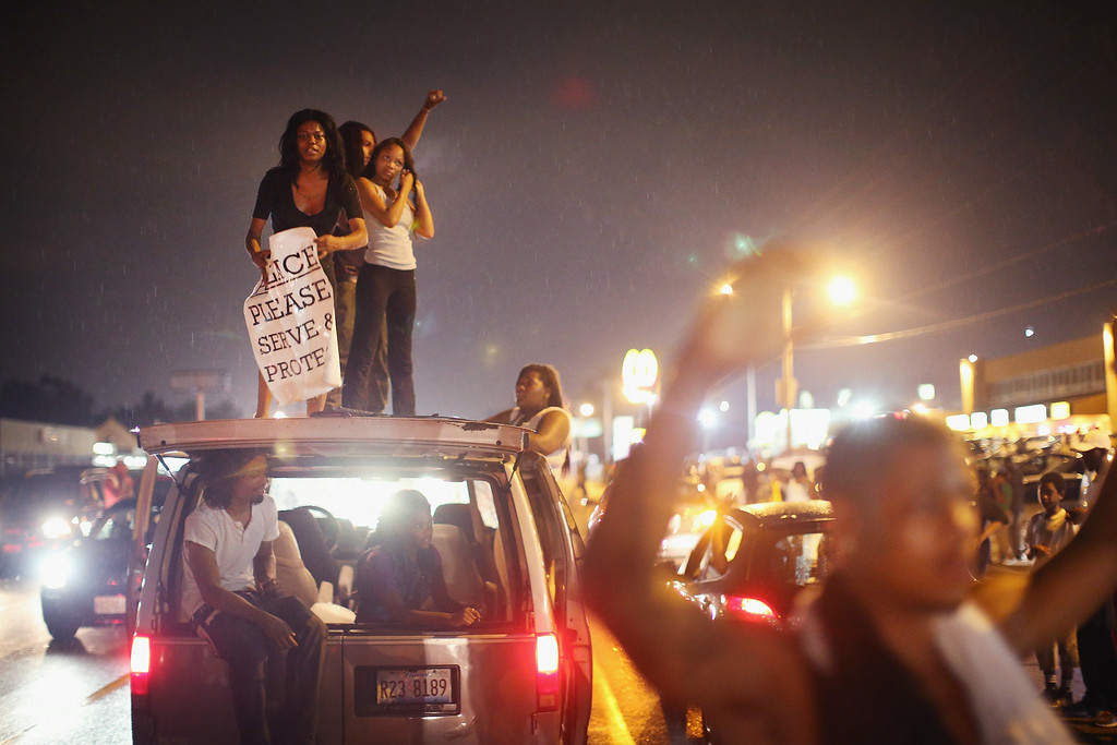 . FERGUSON, MO - AUGUST 15:  Demonstrators gather along West Florissant Avenue to protest the shooting of Michael Brown on August 15, 2014 in Ferguson, Missouri. Brown was shot and killed by a Ferguson police officer on August 9. Tonight\'s demonstration again ended with protestors clashing with police followed by more looting.  (Photo by Scott Olson/Getty Images)