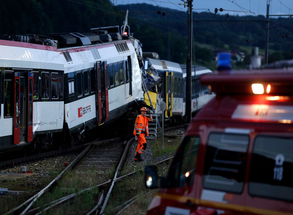 . A rescue worker walks at the site of a head-on collision between two trains near Granges-pres-Marnand, near Payerne in western Switzerland July 29, 2013. The two trains collided in the Swiss canton of Vaud on Monday evening, injuring about 40 people, four seriously, Swiss news agency ATS reported. There was no immediate report of any deaths in the crash. REUTERS/Denis Balibouse