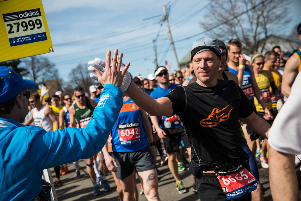 . A runner gives a high five at the beginning of the Boston Marathon on April 21, 2014 in Hopkington, Massachusetts. Today marks the 118th Boston Marathon; security presence has been increased this year, due to two bombs that were detonated at the finish line last year, killing three people and injuring more than 260 others.  (Photo by Andrew Burton/Getty Images)