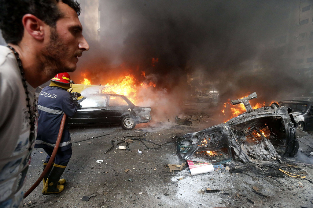 . A man walks past as a firefighter extinguishes fire at the site of an explosion in Beirut\'s southern suburb neighborhood of Bir al-Abed on July 9, 2013.   AFP PHOTO/STR-/AFP/Getty Images