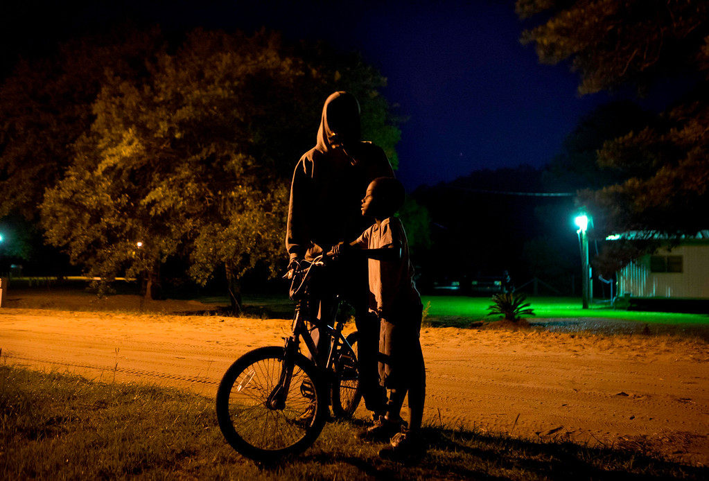 . J.J. Wilson 9, right, and Chris Bailey, 18, play with a bike along one of the main streets in the Hog Hammock community of Sapelo Island, Ga. on Wednesday, May 15, 2013. (AP Photo/David Goldman)