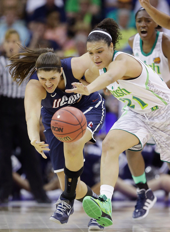 . Connecticut center Stefanie Dolson (31) and Notre Dame guard Kayla McBride (21) chase a loose ball in the first half of the women\'s NCAA Final Four college basketball tournament semifinal, Sunday, April 7, 2013, in New Orleans. (AP Photo/Gerald Herbert)