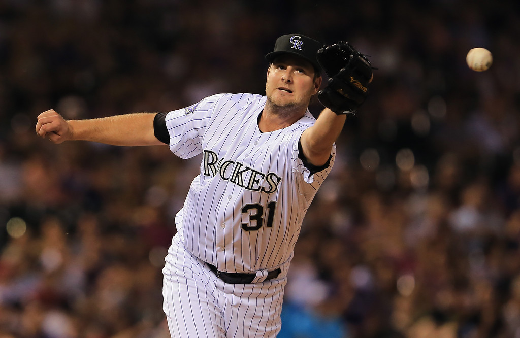 . Relief pitcher Chris Volstad #31 of the Colorado Rockies can\'t get his glove on a ground ball by Ian Desmond #20 of the Washington Nationals that was fielded for an out by second baseman Jonathan Herrera #18 of the Colorado Rockies in the eighth inning at Coors Field on June 12, 2013 in Denver, Colorado.  (Photo by Doug Pensinger/Getty Images)