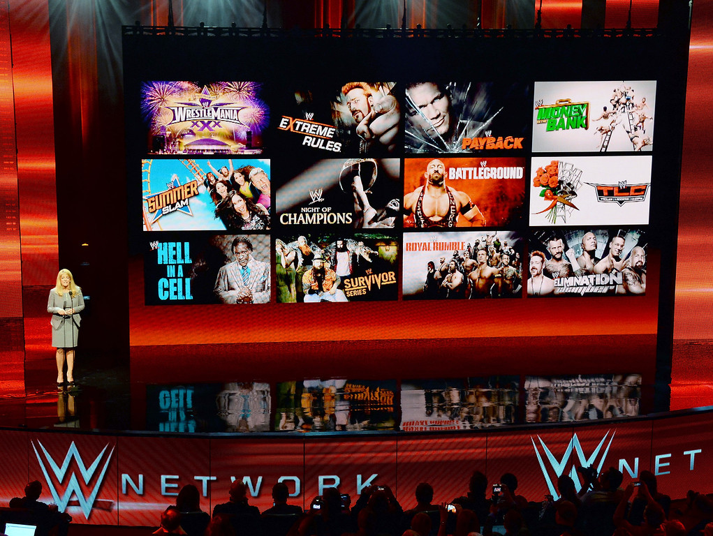 . WWE Chief Revenue and Marketing Officer Michelle Wilson speaks at a news conference announcing the WWE Network at the 2014 International CES at the Encore Theater at Wynn Las Vegas on January 8, 2014 in Las Vegas, Nevada. The network will launch on February 24, 2014 as the first-ever 24/7 streaming network, offering both scheduled programs and video on demand. The USD 9.99 per month subscription will include access to all 12 live WWE pay-per-view events (pictured on screen) each year. CES, the world\'s largest annual consumer technology trade show, runs through January 10 and is expected to feature 3,200 exhibitors showing off their latest products and services to about 150,000 attendees.  (Photo by Ethan Miller/Getty Images)