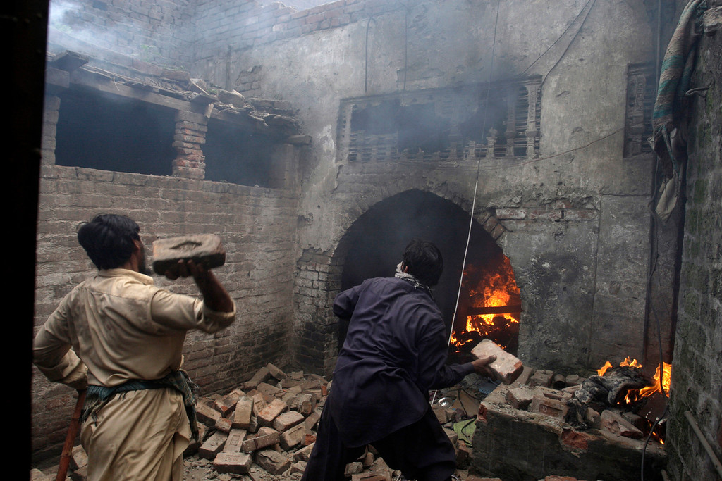 . Pakistani men, part of an angry mob, throw bricks at a Christian house after setting it on fire, in Lahore, Pakistan, Saturday, March 9, 2013. A mob of hundreds of people in the eastern Pakistani city of Lahore attacked a Christian neighborhood Saturday and set fire to homes after hearing accusations that a Christian man had committed blasphemy against Islam\'s prophet, said a police officer. (AP Photo/K.M. Chaudary)
