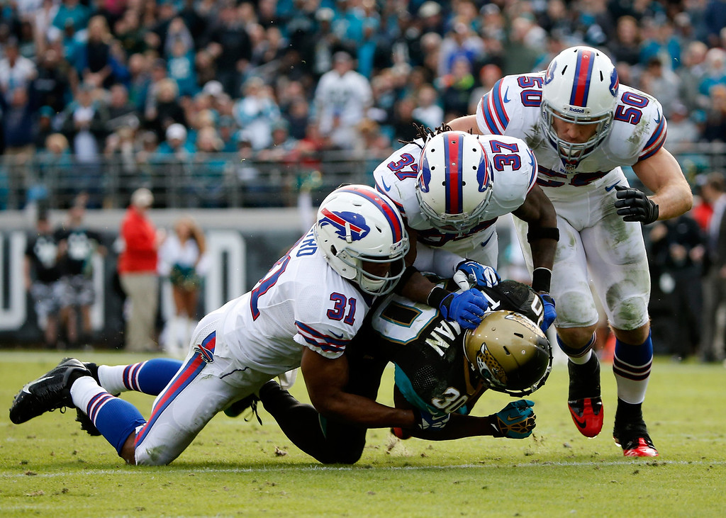 . Jordan Todman #30 of the Jacksonville Jaguars is tackled by  Jairus Byrd #31,  Nickell Robey #37, and  Kiko Alonso #50 of the Buffalo Bills during the game at EverBank Field on December 15, 2013 in Jacksonville, Florida.  (Photo by Sam Greenwood/Getty Images)