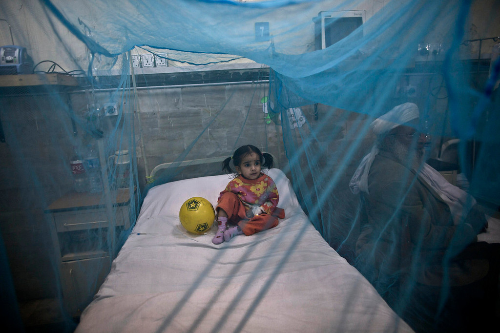 . A Pakistani child suffering from the mosquito-borne disease, dengue fever, rests in a bed covered with a net at an isolation ward of a hospital in Rawalpindi, Pakistan, Monday, Nov. 11, 2013. Dengue, a flu-like illness is spread by the Aedes mosquito and spikes during the annual monsoons, when the rains leave puddles of stagnant water where the insects breed. (AP Photo/Muhammed Muheisen)