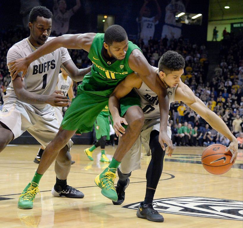 . Colorado Buffaloes guard Askia Booker (0) steals the ball away from Oregon Ducks guard Mike Moser (0) during the first half January 5, 2014 at Coors Events Center. (Photo by John Leyba/The Denver Post)