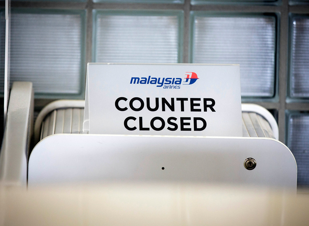 . A closed desk of Malaysian airlines is seen at Schiphol airport in Amsterdam, Thursday, July 17, 2014. Ukraine said a passenger plane carrying 295 people was shot down Thursday as it flew over the country, and both the government and the pro-Russia separatists fighting in the region denied any responsibility for downing the plane. (AP Photo/Phil Nijhuis)
