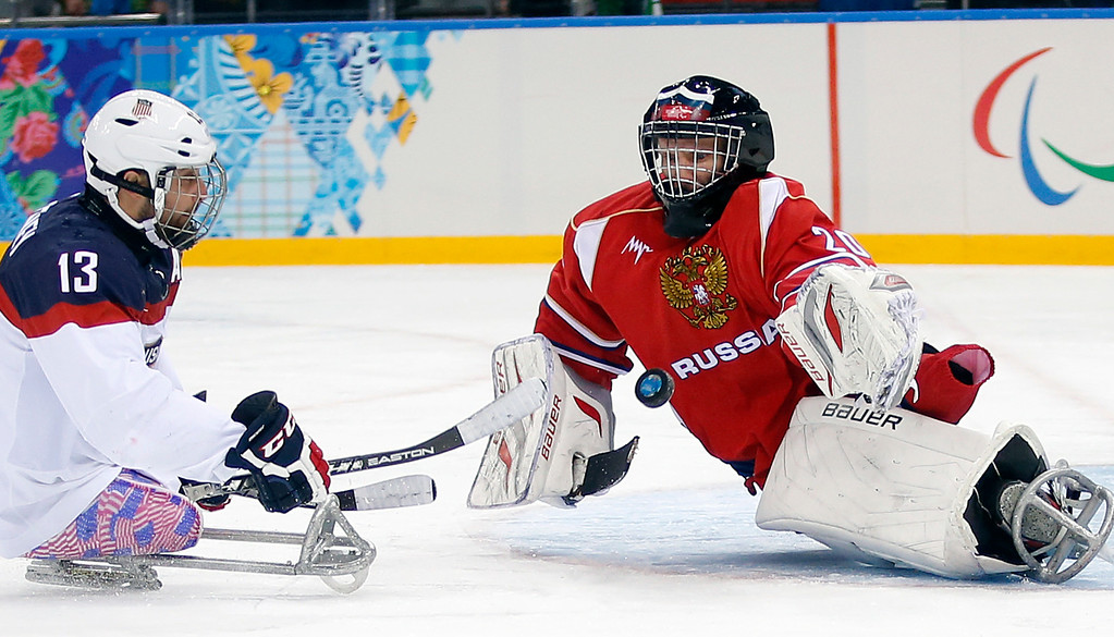 . United States\'s Joshua Sweeney, left, shots on goal as Russia\'s Vladimir Kamantcev, right, try to defend during the gold medal ice sledge hockey match between United States and Russia at the 2014 Winter Paralympics in Sochi, Russia, Saturday, March 15, 2014. (AP Photo/Pavel Golovkin)