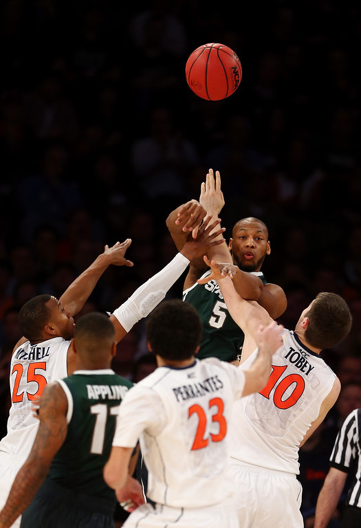 . Adreian Payne #5 of the Michigan State Spartans passes the ball against Akil Mitchell #25, London Perrantes #23, and Mike Tobey #10 of the Virginia Cavaliers during the regional semifinal of the 2014 NCAA Men\'s Basketball Tournament at Madison Square Garden on March 28, 2014 in New York City.  (Photo by Elsa/Getty Images)