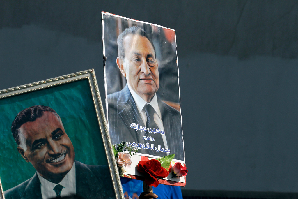 """. Supporters of Egypt\'s former President Hosni Mubarak raise his poster and one of late President Gamal Abdel Nasser, left, in front of Torah Prison where Mubarak has been held, in Cairo, Egypt, Thursday, Aug. 22, 2013. Arabic writing on the poster reads \""""Mubarak lovers.\"""" Egypt\'s ousted leader Hosni Mubarak, wearing a white shirt and loafers while flashing a smile, was released from prison Thursday and transported to a military hospital in a Cairo suburb where he will be held under house arrest. (AP Photo/Amr Nabil)"""