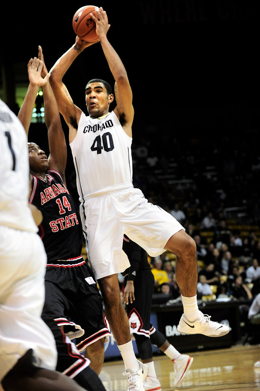 . University of Colorado\'s Josh Scott (40) drives against Arkansas State\'s Kelvin Downs (14) during their game at the Coors Events Center on the CU Boulder Campus in Boulder, Colorado on November 18, 2013.  Photo by Paul Aiken / The Boulder Daily Camera.